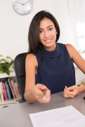 cheerful young brunette business woman customer inviting to sign contract